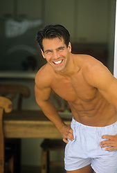 sexy man with a great smile, no shirt and wearing boxer shorts at home