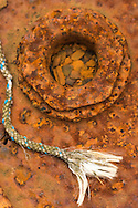 A frayed rope lies against dark rusted metal in a boat repair yard