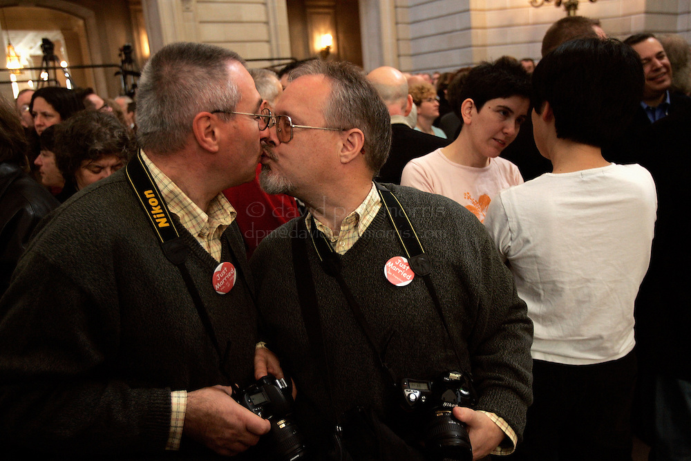 SAN FRANCISCO - FEBRUARY 12: Fernando Orlandi (L) and Bill Wilson who have been married for one year and together for 19 years  kiss as they and other Gay and Lesbian couples who were married last year attend the 1st wedding anniversary bash hosted by Mayor Gavin Newsom in City Hall on Saturday February 12, 2004. Several thousand couples along with their family and friends attended the morning event which will include celebrations throughout the day.  Photograph by David Paul Morris