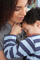 Boy (5-6) sleeping in mother's arms
