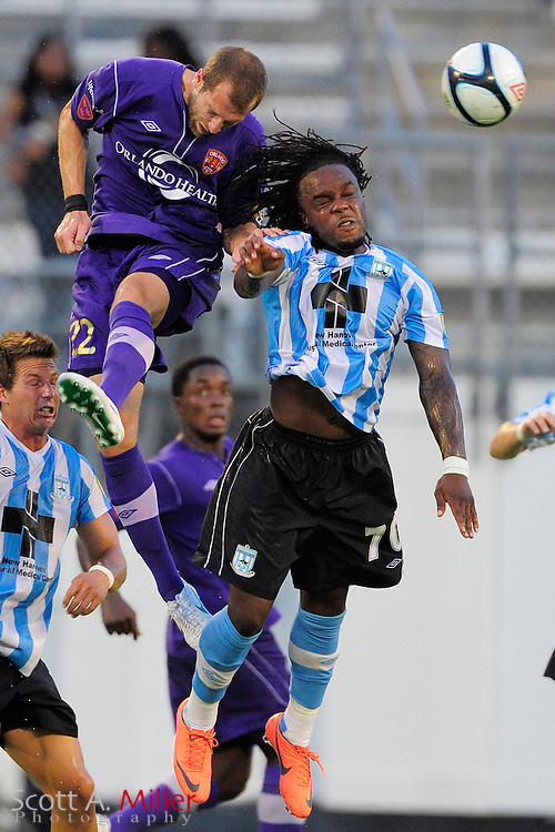 Orlando City Lions defender Rob Valentino (22) and Wilmington Hammerheads forward Chukwudi Chijindu (70) go airborne for a ball during their game at the Florida Citrus Bowl on July 25, 2012 in Orlando, Florida. ..©2012 Scott A. MIller)
