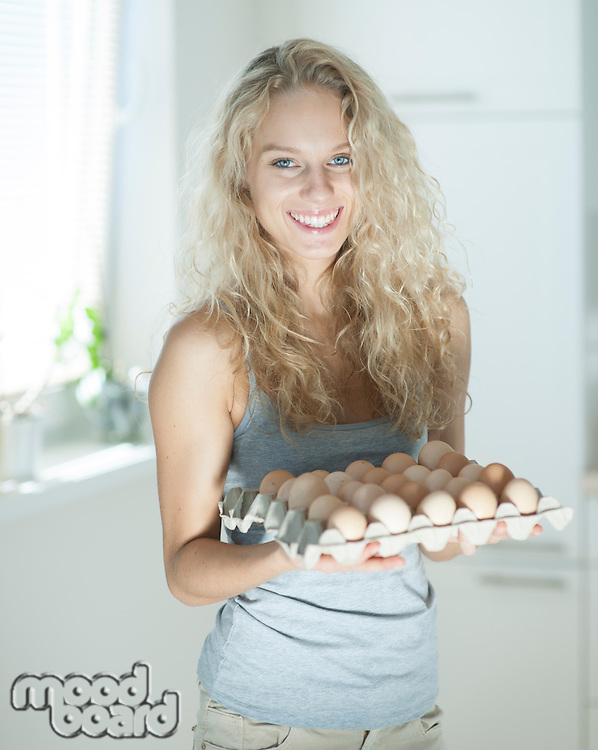 Portrait of woman carrying eggs in kitchen