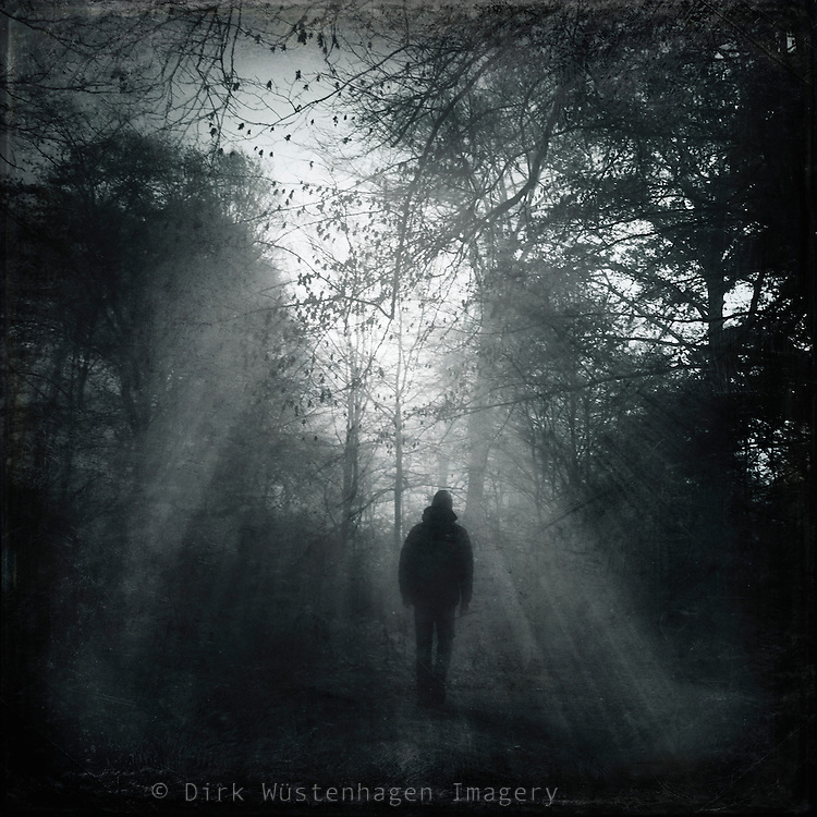 Man walking in a forest towards the light - black and white photograph with textures