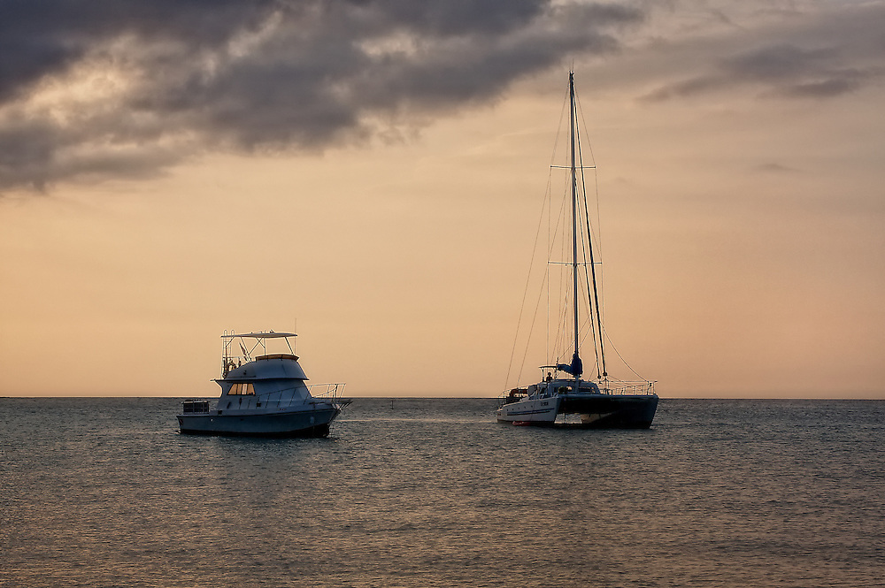 A sailboat and yacht anchored close to shore during sunset.