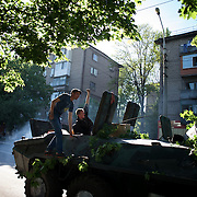 Pro-Russian activists celebrate after successfully fixing the engine of an armoured personal carrier left behind by the Ukrainian army the day before due to a faulty engine as fighting between Ukrainian troops and armed separatist groups erupted.