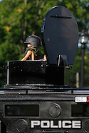 Julian Sample wears an oversized helmet while he peers from the top of a police armored vehicle at the New Britain National Night Out event at Willow Street Park. (Photo by Kevin Bartram)