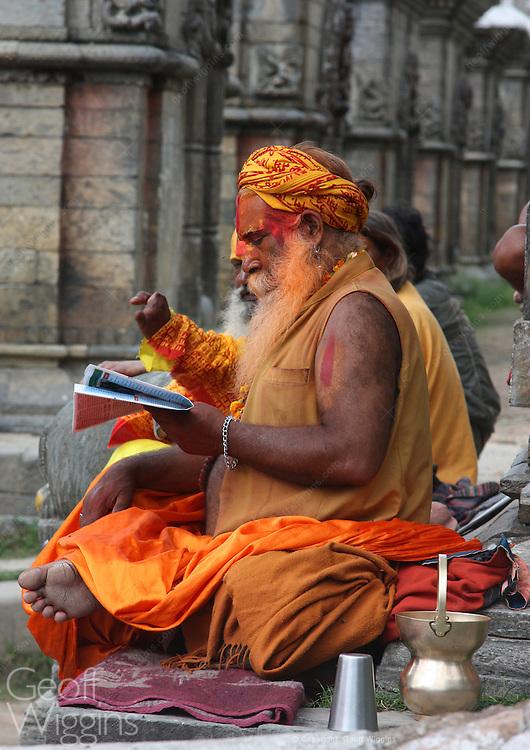 One handed Sadu holy man reads newspaper at Kathmandu's Pashupatinath temple, Nepal