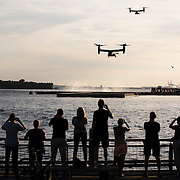 September 24, 2015 - New York, NY : People standing on Pier 11 watch two Ospreys carrying the pope's cavalcade arrive on 6 East River Piers in Manhattan on Thursday evening. Pope Francis arrived via helicopter from John F. Kennedy Airport, at 6 East River Piers in lower Manhattan on Thursday early evening, September 24.  CREDIT: Karsten Moran for The New York Times