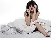 one young woman in bed awakening tired insomnia hangover  in a white sheet bed on white background