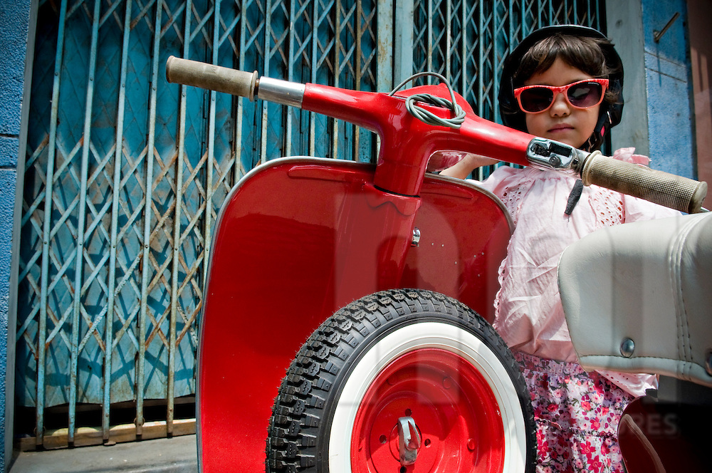 Little caucasian girl with sunglasses poses along a vintage vespa. Ho Chi Minh, Vietnam, Asia