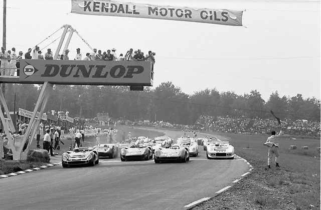 Start of the 1966 USRRC race at Watkins Glen. Winner was Buck Fulp in Lola no. 26 from pole starter Jerry Grant in no. 8. Famous lavender suited starter Tex Hopkins flees with his flag.