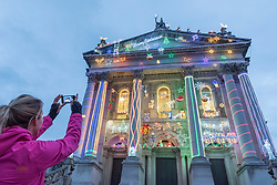 "© Licensed to London News Pictures. 01/12/2017. London, UK.  A commuter views Alan Kane's new work, ""Home for Christmas"", which has been unveiled at Tate Britain.  ""Home for Christmas"" transforms the exterior of the gallery into a glowing display of off-the shelf decorations with an arrangement of LED Santas, reindeer, snowmen and Christmas trees, along with 'Merry Christmas' and 'Santa Stop Here' signs.  The artwork will be switched on daily from 2 December 2017 to 6 January 2018.  Photo credit: Stephen Chung/LNP"