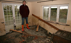 © London News Pictures. 06/03/2014. Moorland, UK. Malcolm and Julie Shovel pictured in their home Sunnybank near Moorland in Somerset. after returning to asses damage cause by flooding. Photo credit: Jason Bryant/LNP. Photo credit : Jason Bryant/LNP