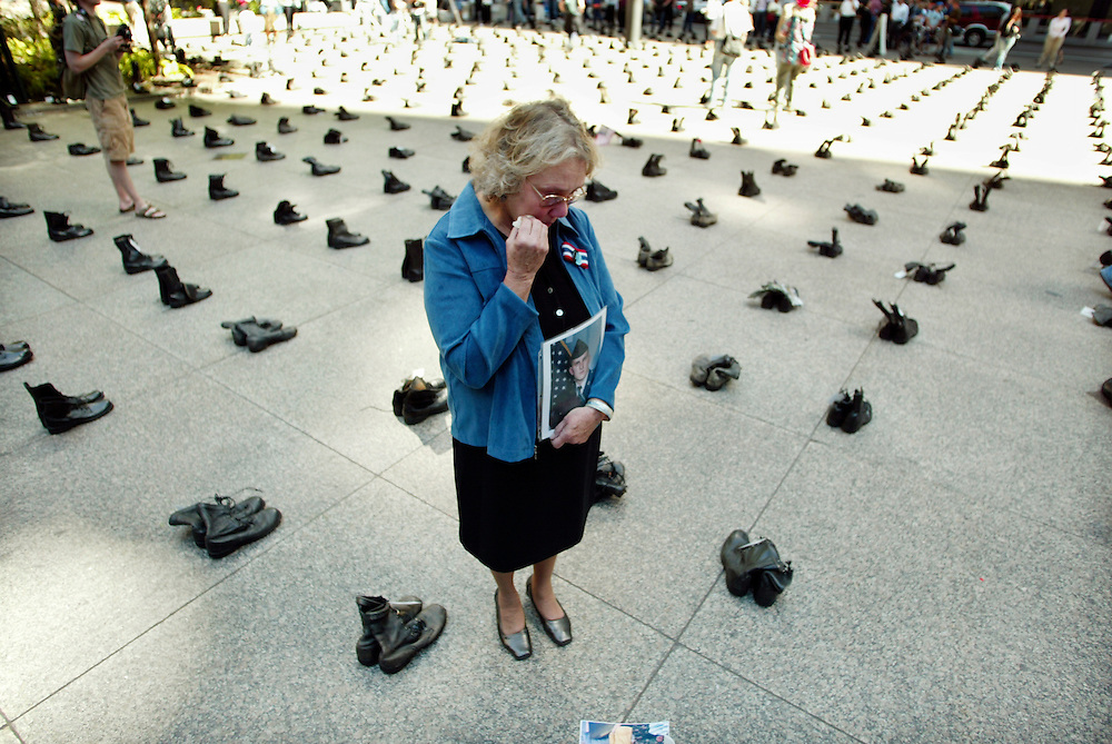 "Celeste Zappala of Philadelphia stands over a combat boot tagged with the name of her son Sherwood Baker holding his photograph in the middle of an exhibit of over 1000 pairs of combat boots bearing name tags of U.S. soldiers killed in Iraq.  The boots fill Federal Plaza in Chicago as part of an exhibit called ""Eyes Wide Open: The Human Cost of War in Iraq"".   The exhibit was put on by the American Friends Service Committee.  For more information see www.eyes.afsc.org.  Baker, a national guardsman,  was 30 when he was killed in an explosion on April 26th of this year.  He was married and had a nine-year-old son.  Zappala says, ""This war was a mistake, a disaster.  It was a betrayal.""  She continues, ""I don't think the administration has any idea what they've let loose or how to solve it."""