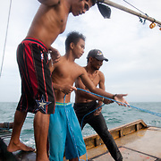 Joseph and Abelino pstrats pulling the trawl at the orders of captain Joan. Joseph is 17 and works like his father did on the sea as a fisherman. The catch of the day is hauled in by the entire crew to be sorted out on deck and taken straight to the market in Hinigaran. The catch that day made the crew $12.00 each( Captain Joan $24.00) One day a week Joseph goes to Alternative Learning schooling provided by Quidan-Kaisahan.  Quidan-Kaisahan is a charity working in Negros Occidental in the Philippines. Their aim is to keep children out of work to secure them education.