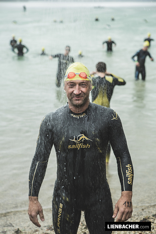 a competitor is havinga shower in the rain before he swims across the Lake (4,2km)