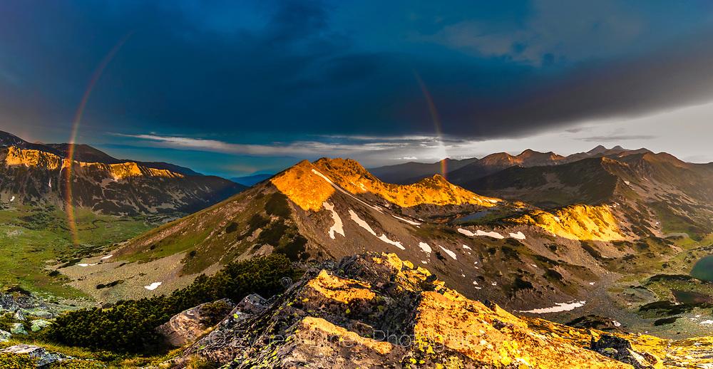 Full rainbow around a mountain peak st sunrise