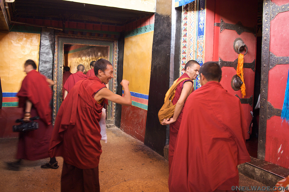 Tibetan monks joke as the gather for a chanting session in the Jokhang in Lhasa, Tibet.