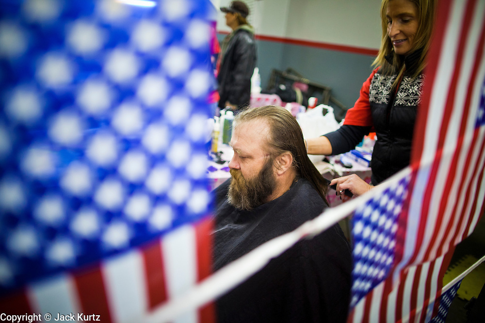 04 FEBRUARY 2011 - PHOENIX, AZ: AMBER BILLINGS, from Phoenix, cuts the hair of homeless US Army vet at the Arizona StandDown in Phoenix Friday. The vet said it was his first haircut in about 10 years. The ArizonaStandDown is an annualthree day event that brings together theValley's homeless and at-risk militaryveterans, connecting themwith services ranging from: VA HealthCare, mental health services, clothing, meals, emergency shelter, transitional and permanent housing,ID/ drivers license's, court services and Legal Aide, showers, haircuts and myriad other services and resources. Arizona StandDown isheld annually at theVeterans Memorial Coliseum at the Arizona State Fairgrounds in Phoenixon Super Bowl weekend.    Photo by Jack Kurtz