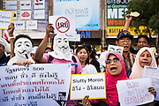 "09 JUNE 2013 - BANGKOK, THAILAND: A Thai Muslim women, and other members of the White Masks, protest against the government of Yingluck Shinawatra at Central World. The White Mask protesters wear the Guy Fawkes mask popularized by the movie ""V for Vendetta"" and the protest groups Anonymous and Occupy. Several hundred members of the White Mask movement gathered on the plaza in front of Central World, a large shopping complex at the Ratchaprasong Intersection in Bangkok, to protest against the government of Thai Prime Minister Yingluck Shinawatra. They say that her government is corrupt and is a ""puppet"" of ousted (and exiled) former PM Thaksin Shinawatra. Thaksin is Yingluck's brother. She was elected in 2011 when her brother endorsed her.       PHOTO BY JACK KURTZ"
