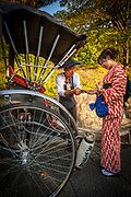 Rickshaw driver gets paid by woman in kimono after tour of Kyoto, Japan.