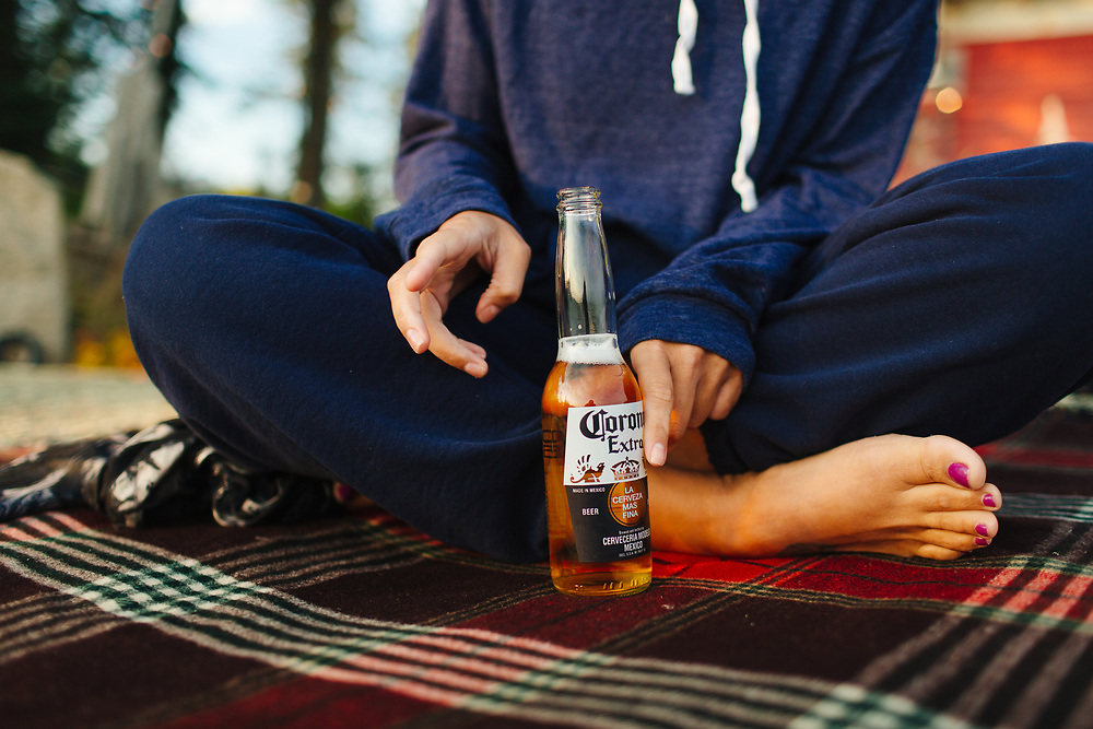 Woman drinking beer on blanket outdoors