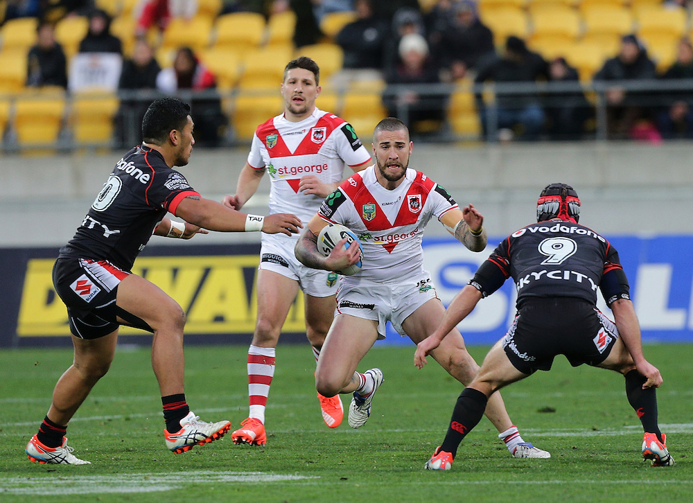 Joel Thompson of the Dragons is challenged by Albert Vete, left, and Nathan Friend of the New Zealand Warriors during their round 22 NRL match at Westpac  Stadium, Wellington on  Saturday, August 08, 2015. Credit: SNPA / David Rowland