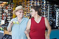 Senior couple trying on funny sunglasses, smiling