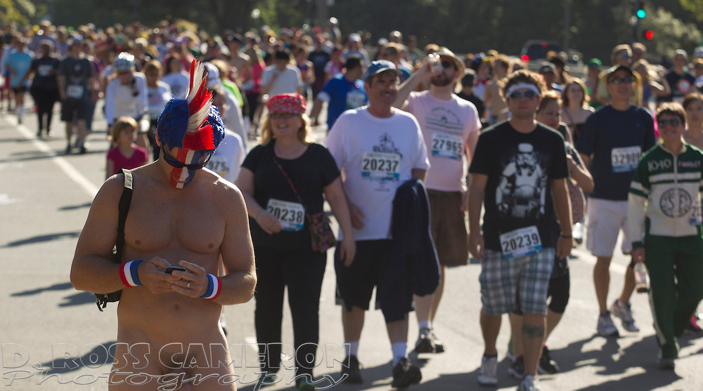 A naked man stops in Golden Gate Park to check his smartphone during the 102nd running of the Bay to Breakers 12K in San Francisco, Sunday, May 19, 2013. More than 30,000 runners -- from the elite to the weekend warrior -- made the 7.62-mile trek from Howard and Spear to the Great Highway. (Photo by D. Ross Cameron)