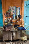 Indian man runs market stall in alleyway in the city of Varanasi, Benares, Northern India