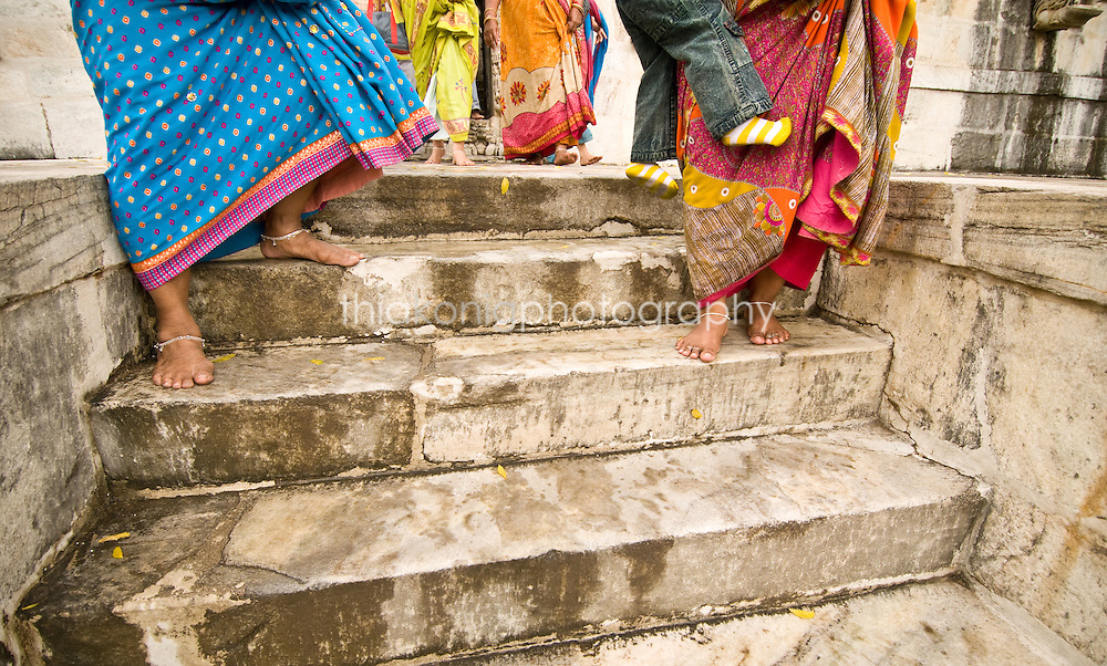 Women with barefeet and ankle bracelets walking down the white marble steps of a Jain Temple, India. The Jains are a sect of Hindu that are so strictly vegetarian, that they wear face masks to prevent accidentally breathing in the smallest of  bugs, and they sweep every step they take to prevent stepping on anything living that might have been in their path.