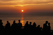dramatic view of a sunset with people silhouetted in foreground