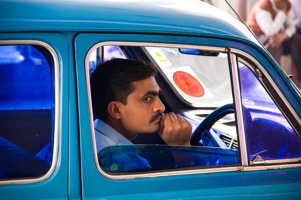 Bored driver in a government car, waiting outside Old Delhi Train Station, India.