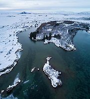 Höfði and Kálfastrandavogar at Lake Mývatn. Winter aerial drone shot. North Iceland.
