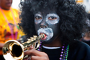 One of the children with painted faces among the members of the Zulu Social Aid and Pleasure Club as they prepare for the Krewe of Zulu Parade on Mardi Gras day near Claiborne Avenue in New Orleans, Louisiana, USA.