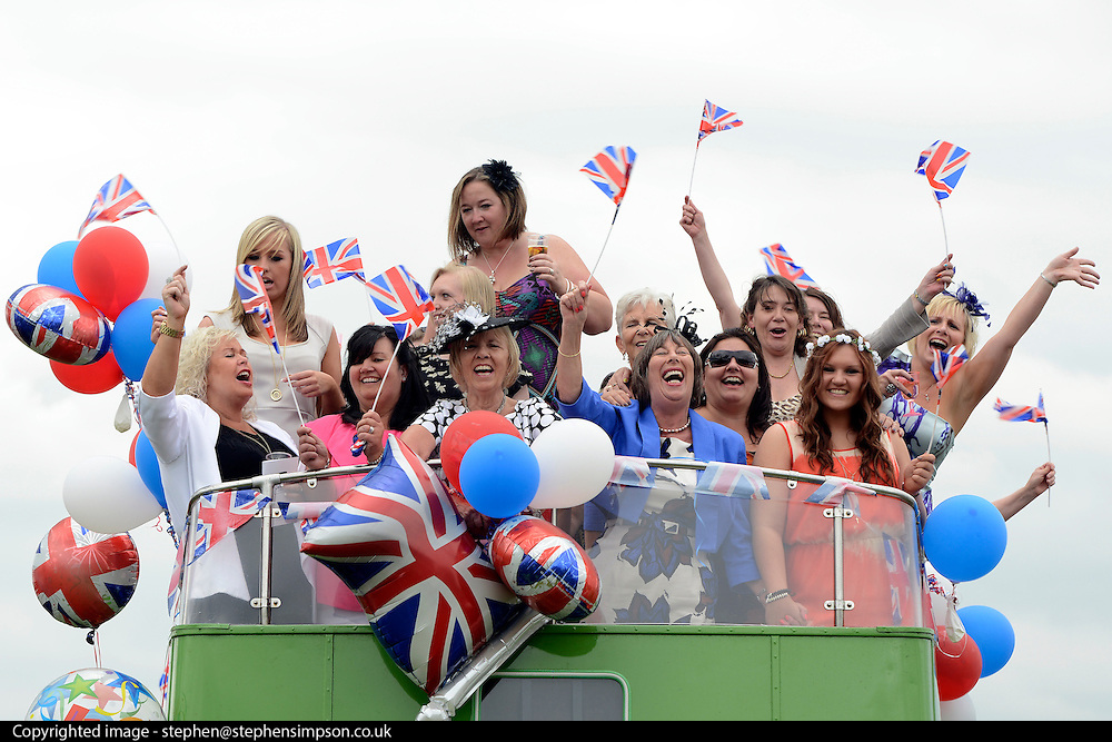 © Licensed to London News Pictures. 01/06/2012. Epsom , UK Ladies wave flags and balloons during a party  on board a private open top double decker bus. Ladies Day today 1st June 2012 at Epsom 2012 Investic Derby Festival. The Queen will attend tomorrow's race meet as part of the 60th Jubilee celebrations. Photo credit : Stephen Simpson/LNP