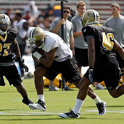 July 29, 2011; Metairie, LA, USA; New Orleans Saints running back Pierre Thomas (23) runs between cornerback Malcolm Jenkins (27) and safety DeAndre McDaniel (46) during the first day of training camp at the New Orleans Saints practice facility. Mandatory Credit: Derick E. Hingle