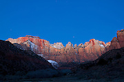 The peaks that comprise the Towers of the Virgin in Zion National Park, Utah, are illuminated by alpenglow, about a half hour before sunrise. The peaks, including the West Temple, Sundial and Altar of Sacrifice, all rise more than 3,500 feet from the Zion Canyon valley floor. The West Temple, the tallest, is 7,810 feet tall.