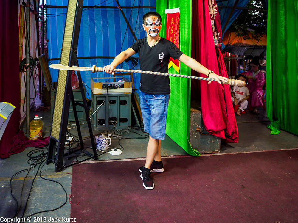 26 AUGUST 2018 - GEORGE TOWN, PENANG, MALAYSIA: A performer rehearses a fight scene before a Hokkien style Chinese opera on the Lim Jetty in George Town for the Hungry Ghost Festival. The opera troupe came to George Town from Fujian province in China. The Hungry Ghost Festival is a traditional Buddhist and Taoist festival held in Chinese communities throughout Asia. The Ghost Festival, also called Ghost Day, is on the 15th night of the seventh month (25 August in 2018). During the Hungry Ghost Festival, the deceased are believed to visit the living. In many Chinese communities, there are Chinese operas and puppet shows and elaborate banquets are staged to appease the ghosts.     PHOTO BY JACK KURTZ