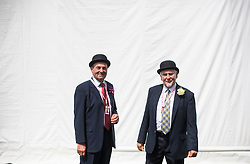 © Licensed to London News Pictures. 04/07/2018. Henley-on-Thames, UK. Two stewards pose for the camera on day one of the Henley Royal Regatta, set on the River Thames by the town of Henley-on-Thames in England. Established in 1839, the five day international rowing event, raced over a course of 2,112 meters (1 mile 550 yards), is considered an important part of the English social season. Photo credit: Ben Cawthra/LNP