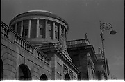 "The Four Courts..1971..16.04.1971..04.16.1971..16th April 1971..The Four Courts,for centuries,has been the centre of Ireland's Judicial system..Work based on the designs of Thomas Cooley, architect of the Royal Exchange (now City Hall), began in 1776. Cooley's building concentrated in the area of the west courtyard and was intended to house only the Public Records Office and King's Inns. When Cooley died in 1784, James Gandon, architect of the Custom House, was appointed to add the courts to the plan. Into his completed design he incorporated Cooley's building, adding two quadrangles and a central block. The quadrangles were given to the record and legal offices, the centre to the four courts of Chancery, Exchequer, Kings Bench and Common Pleas. At the hub is the Round Hall, 64ft in diameter, with inner and outer domes and a surround of Corinthian columns. It was once described as ""both the physical and spiritual centre of the building""(www.courts.ie/courts.ie/library3.).Throughout the years the courts have been damaged ,destroyed and rebuilt as a result of rebellion and the Irish civil war..Here we see an image of the dome and its columns taken from the roadway at Inns Quay."