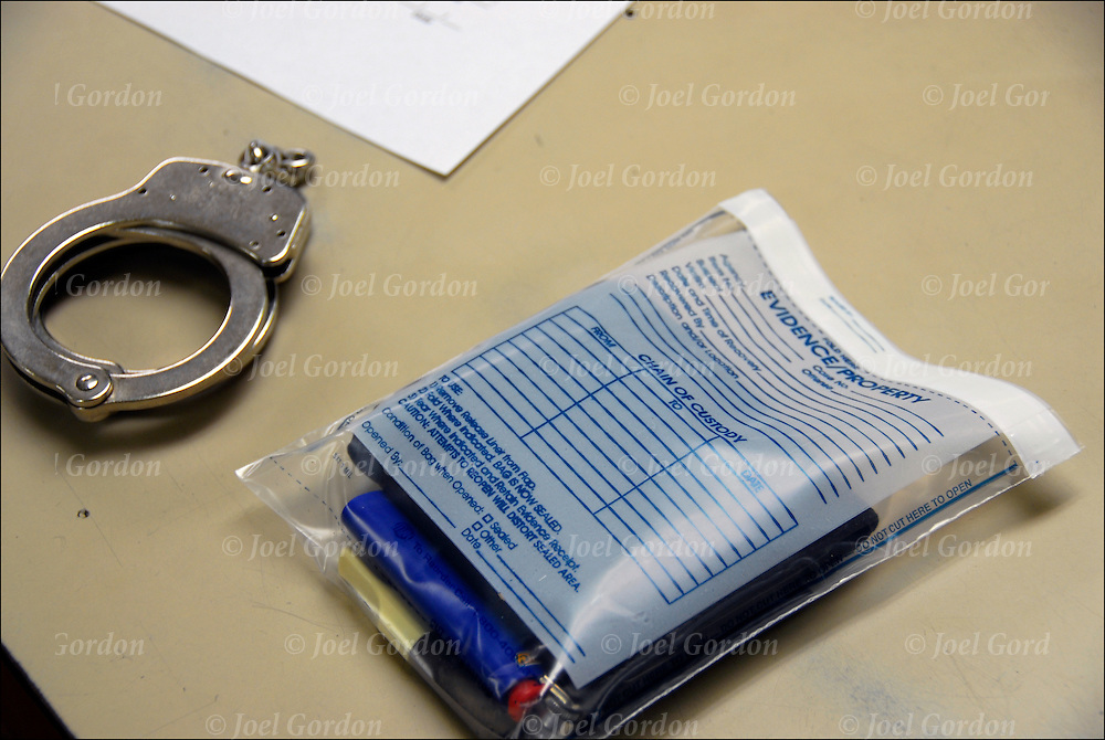 Putnam County Jail, drugs in chain of custody envelope and handcuffs on booking desk.