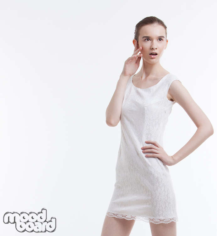 Young woman in dress looking away with hand on hip over white background