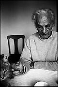 El Poeta Nicanor Parra, famoso por ser el creador de la Anti Poesía, acaricia a su gato durante un almuerzo en su casa de Las Cruces, V Región de Valparaíso, Chile. 2003 (©Alvaro de la Fuente)