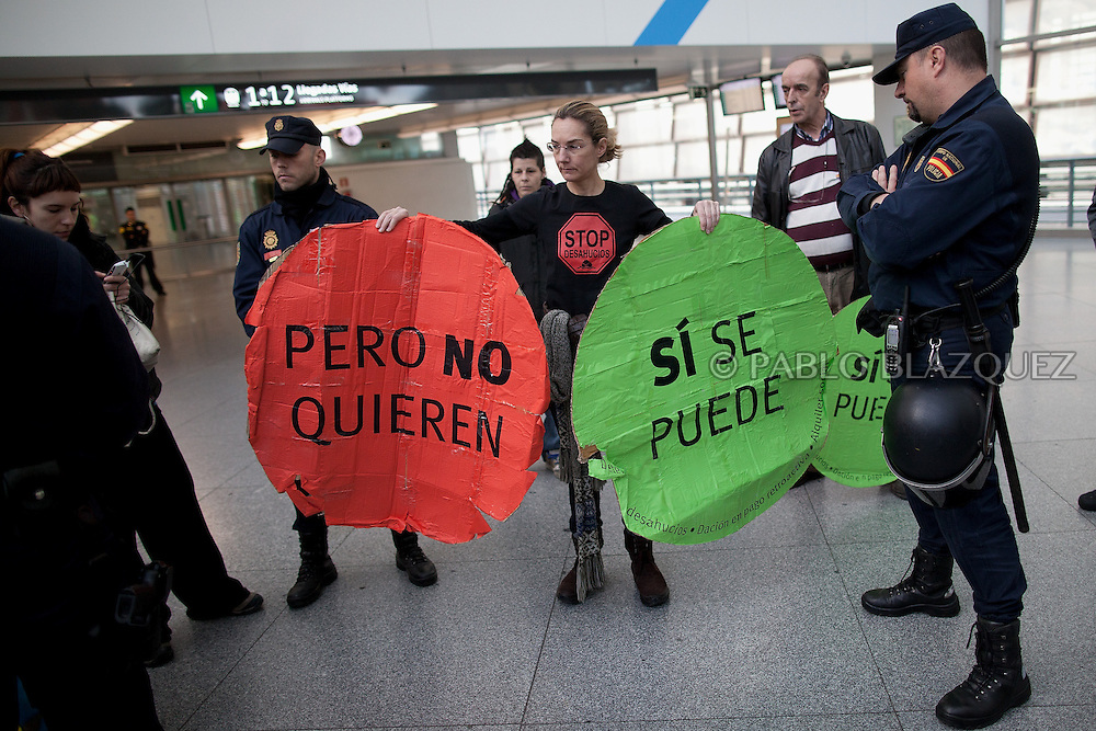 A member of the Mortgage Holder Platform (PAH) holds banners reading 'yes, we can but they don't want' surrounded by riot police during a protest inside Atocha Train Station in Madrid, Spain, Tuesday, on March 19, 2013. Dozens of members of the Mortgage Holders Platform (PAH) wait for deputies arriving to Parliament demanding support for People's Legislative Initiative to stop evictions, allow social rent and debt relief.
