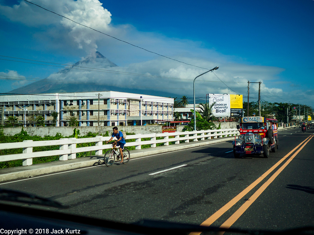 29 JANUARY 2018 - LEGAZPI, ALBAY, PHILIPPINES: Mayon volcano belches a cloud of steam Monday morning as traffic pass Dominican University Bicol in Lagazpi. The volcano's eruptions continued Monday. At last count, more 80,000 people have been evacuated from their homes of the slopes of the volcano and are crowded into shelters in communities outside of the danger zone.    PHOTO BY JACK KURTZ