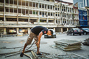 "11 DECEMBER 2012 - BANGKOK, THAILAND:  A worker uses a cutting torch to separate recyclable metals in ""Washington Square"" a notorious entertainment district off Sukhumvit Soi 22 in Bangkok. Demolition workers on many projects in Thailand live on their job site tearing down the building and recycling what can recycled as they do so until the site is no longer inhabitable. They sleep on the floors in the buildings or sometimes in tents, cooking on gas or charcoal stoves working from morning till dark. Sometimes families live and work together, other times just men. Washington Square was one of Bangkok's oldest red light districts. It was closed early 2012 and is being torn down to make way for redevelopment.    PHOTO BY JACK KURTZ"