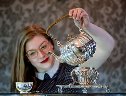 Bonham's staff member Jaine Heggie with a rare silver tea kettle dated 1733 which is coming under the hammer in Edinburgh 14 June.<br /> <br /> &copy; Dave Johnston/ EEm