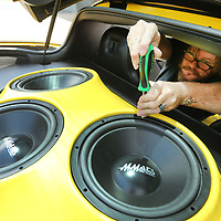Hubbard makes an adjustment as he tightens down the mounting screws on a customer's speaker box that holds three 12 inch MMATS Audio Subwoofers that are powered by a MMATS Audio 1400.1 amplifier. Aside from the intsall, Hubbard also custom built the box to fit inside the hatch area of the customer's 2006 Corvette.