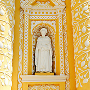 White statue that is part of the distinctive  and ornate yellow and white exterior of the Iglesia y Convento de Nuestra Senora de la Merced in downtown Antigua, Guatemala.